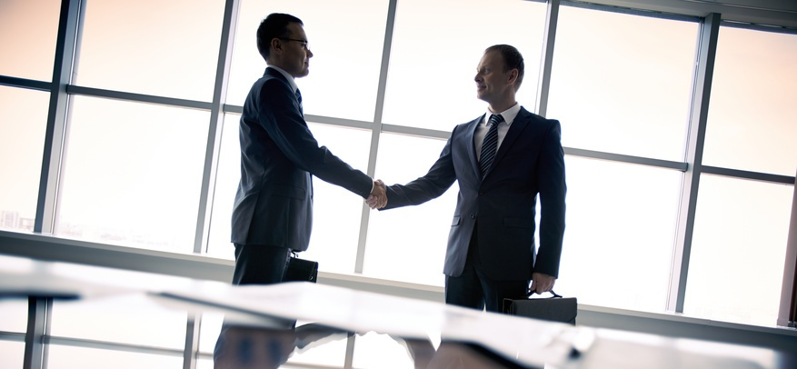 Silhouettes of two businessmen standing by the window and handshaking